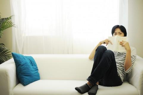 ソファで本を持つ男性