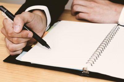 ノートにメモを書く男性